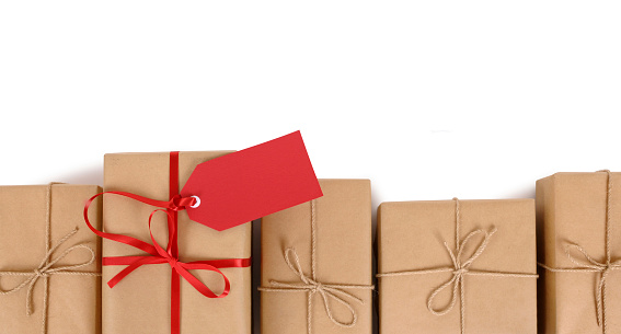 Brown Paper Package With Red Gift Tag In Row Of Plain Ones Stock Photo - Download Image Now