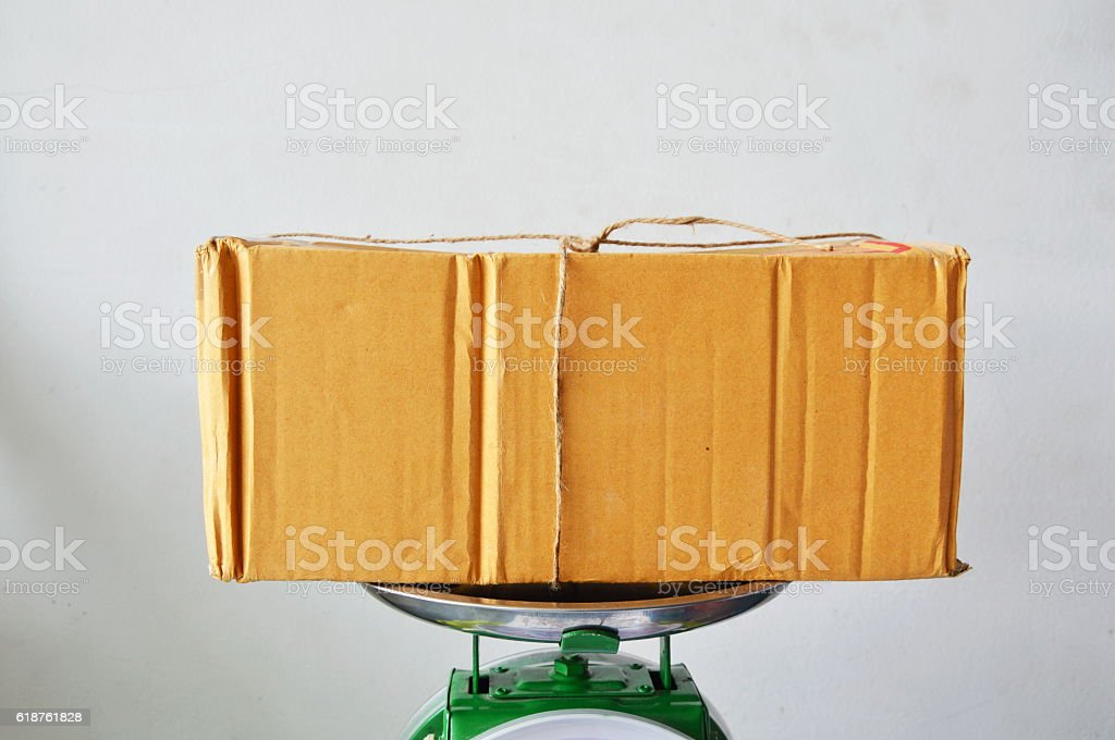 brown paper postbox on weighing scale tray in shop stock photo