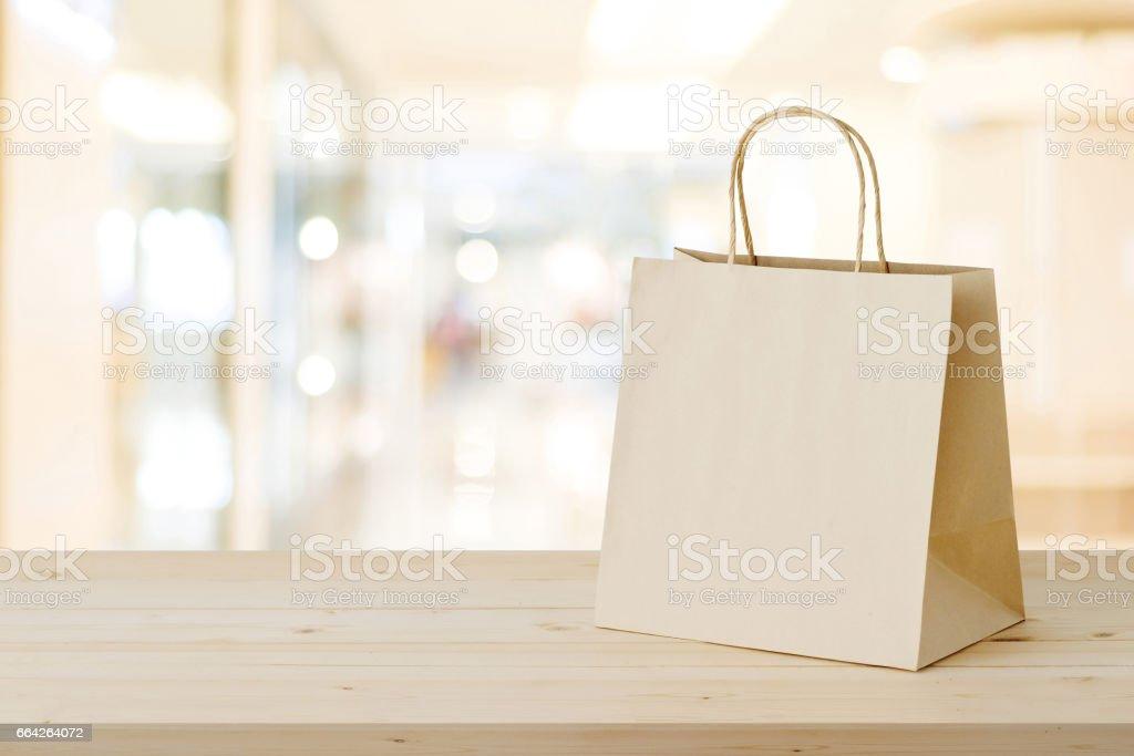 Bolsa de papel marrón en la tabla de madera sobre fondo de tienda borrosa, negocio, plantilla, venta por menor, venta - foto de stock