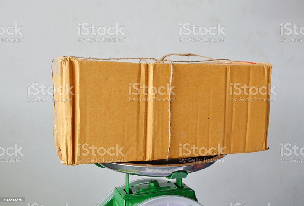 brown postbox on weighing scale tray in shop stock photo
