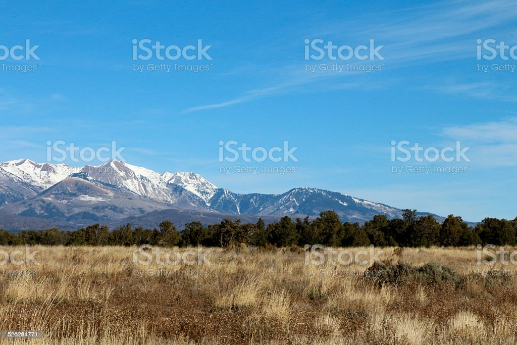 Brown prarie and snow capped mountains stock photo