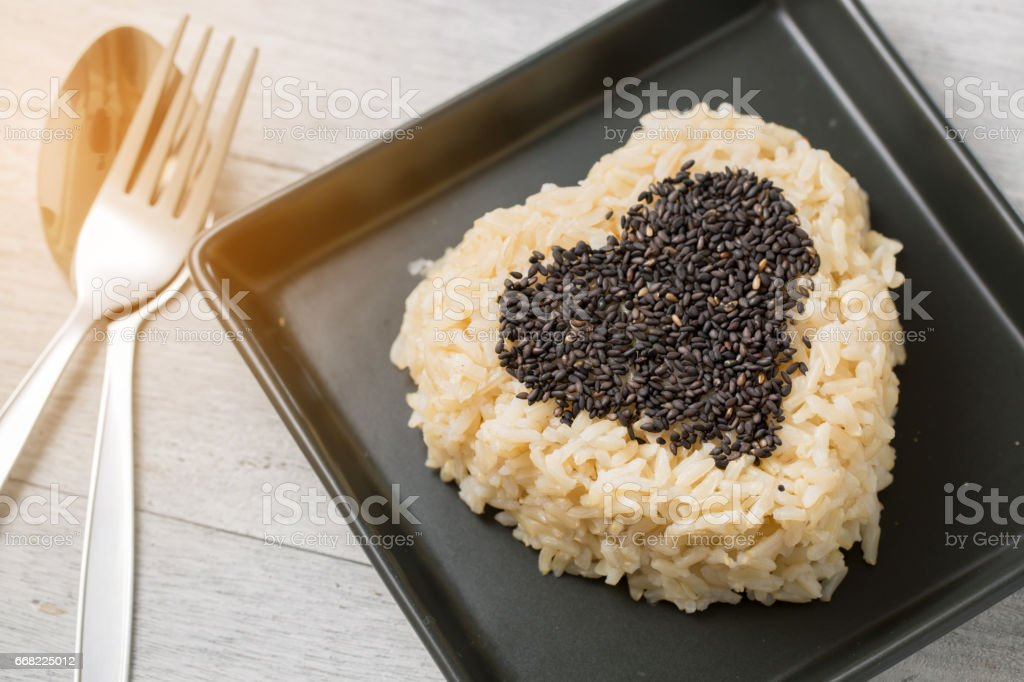brown rice and black sesame heart shape on black plate on wooden background stock photo