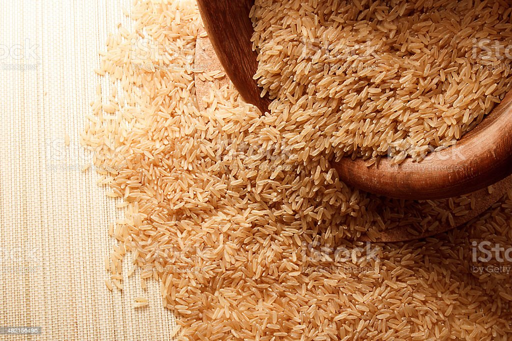 Brown rice falling from a wooden bowl stock photo