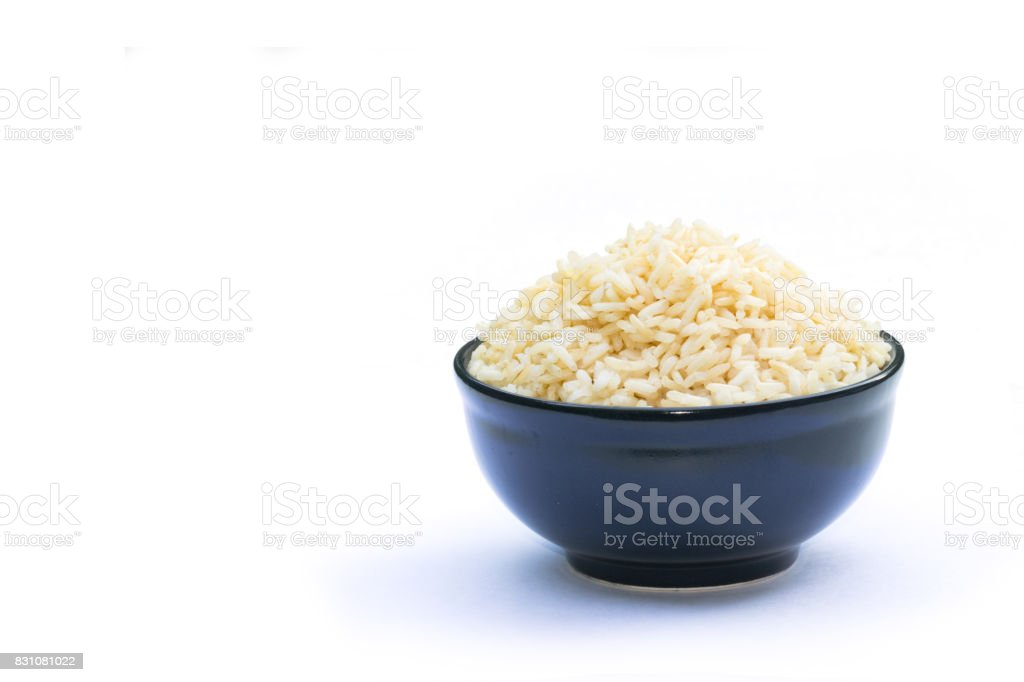Brown rice in black bowl on a white background stock photo