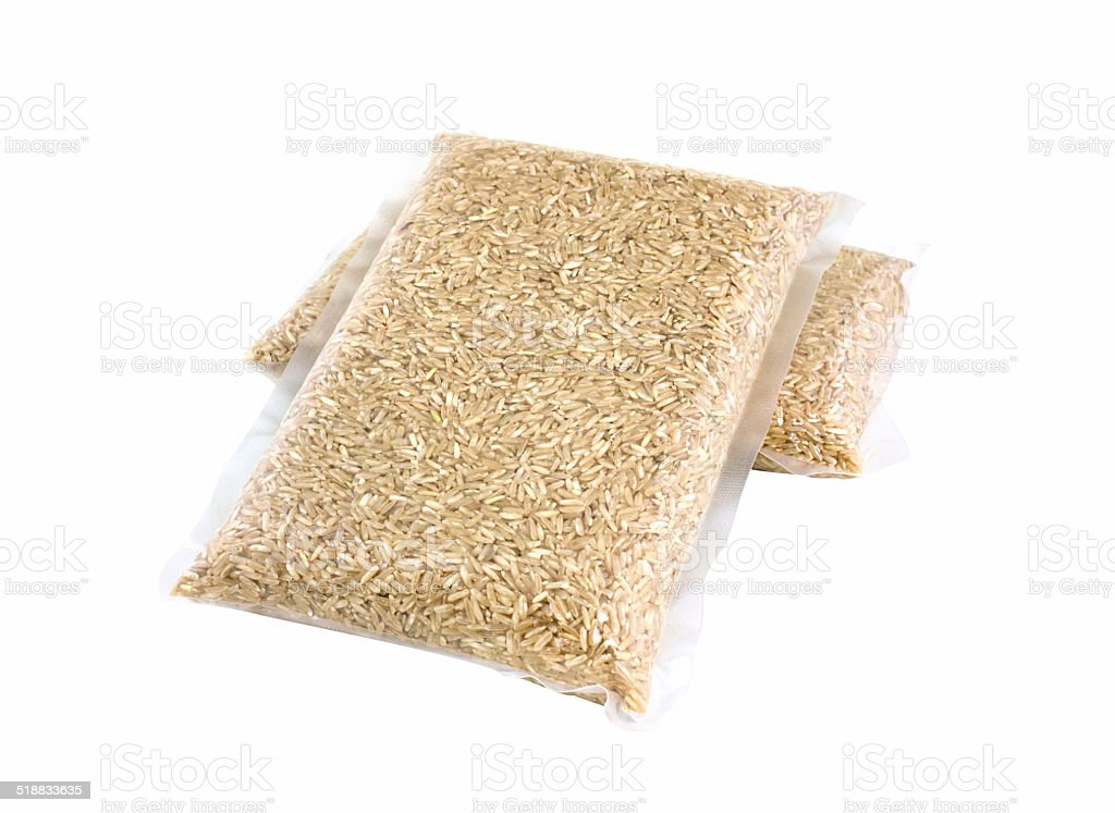 Brown rice in vacuum bag isolated on white background stock photo