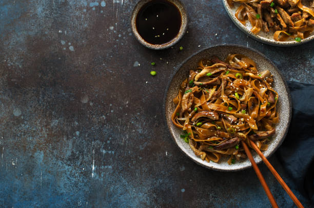 Brown rice noodles , beef, mushrooms and scallions plate on dark stone background stock photo