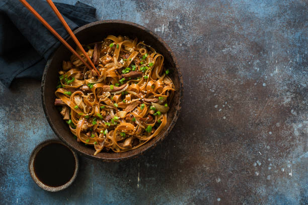 Brown rice noodles stewed with beef, mushrooms and soy sauce stock photo