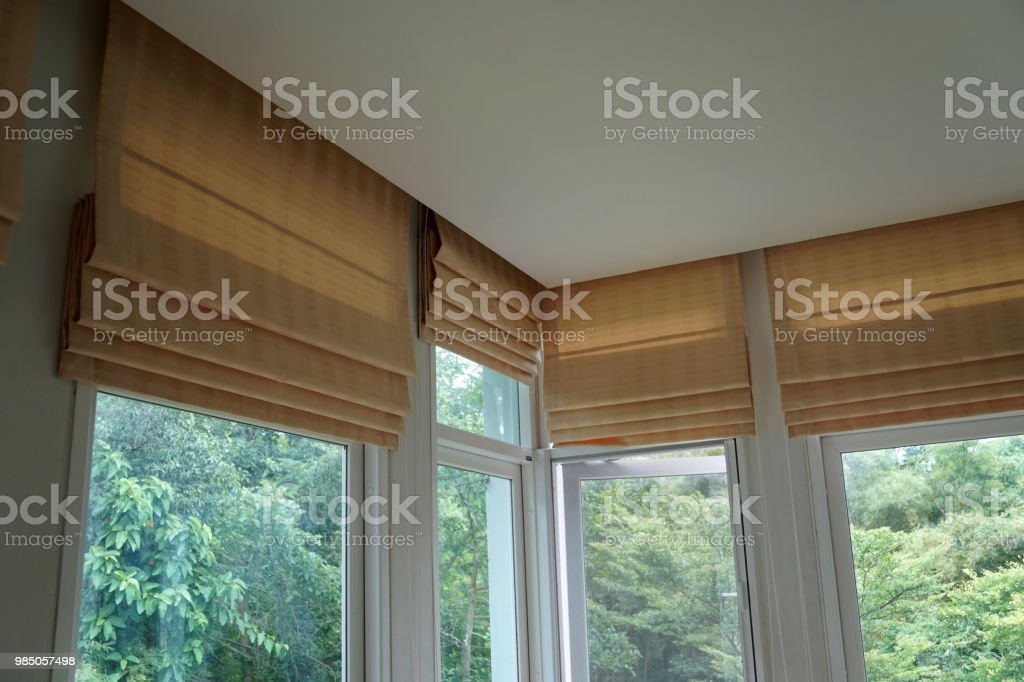 brown roman blind shade curtain and shadow tree forest mountain background stock photo