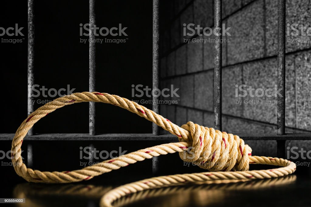 Brown rope noose dark and light on black table with old prison bars cell lock background dark black and light stock photo