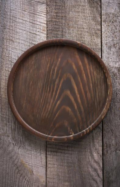 braun runden tablett auf hölzernen hintergrund. ansicht von oben. platz für ihren text. - tablett holz stock-fotos und bilder