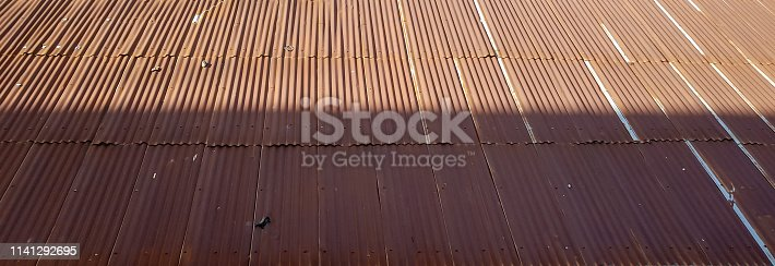 Old brown roof top, made of corrugated metal sheets, covered halfway by sunlight.