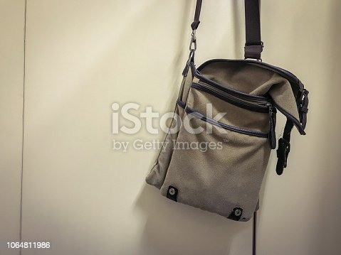 istock Brown shoulder bag hang on white bathroom door 1064811986