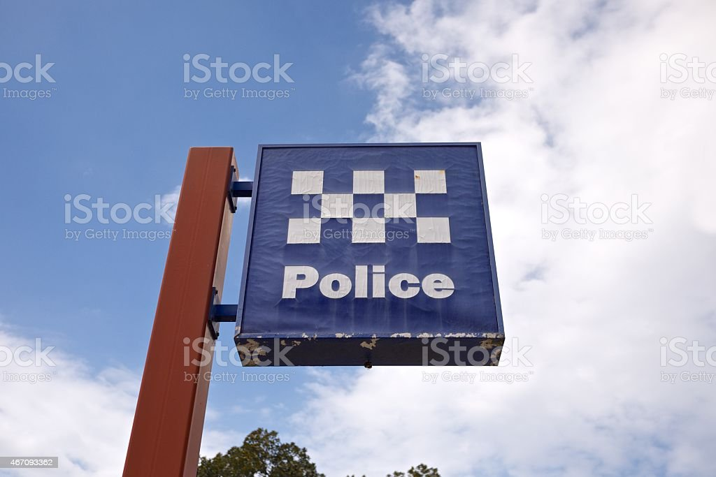 Brown sign post with blue and white police sign stock photo