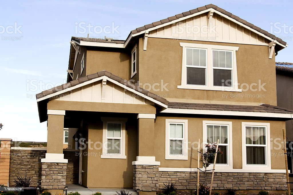 Brown stucco home with white trim against a blue sky stock photo