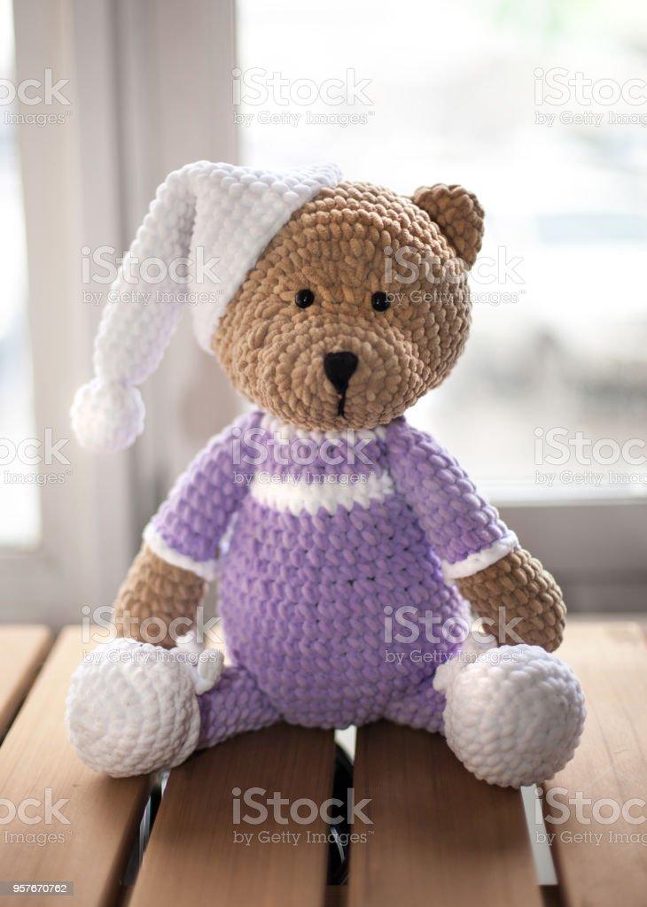Marrón peluche animal osito lila ropa y sombrero blanco en la madera - foto de stock