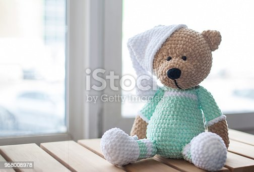 Brown stuffed animal teddy bear in lilac clothes and white hat on the wood.