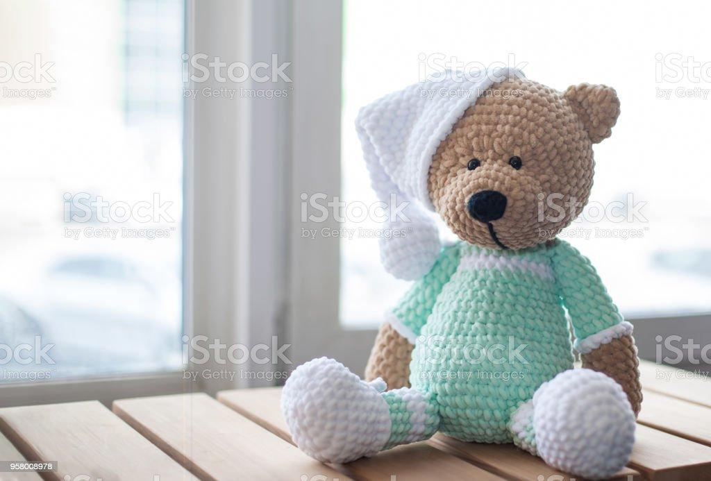 Marrón peluche animal oso de peluche en color menta ropa y sombrero blanco en la madera. - foto de stock
