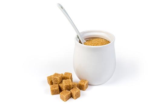 Brown sugar cubes and brown granulated sugar in sugar-bowl