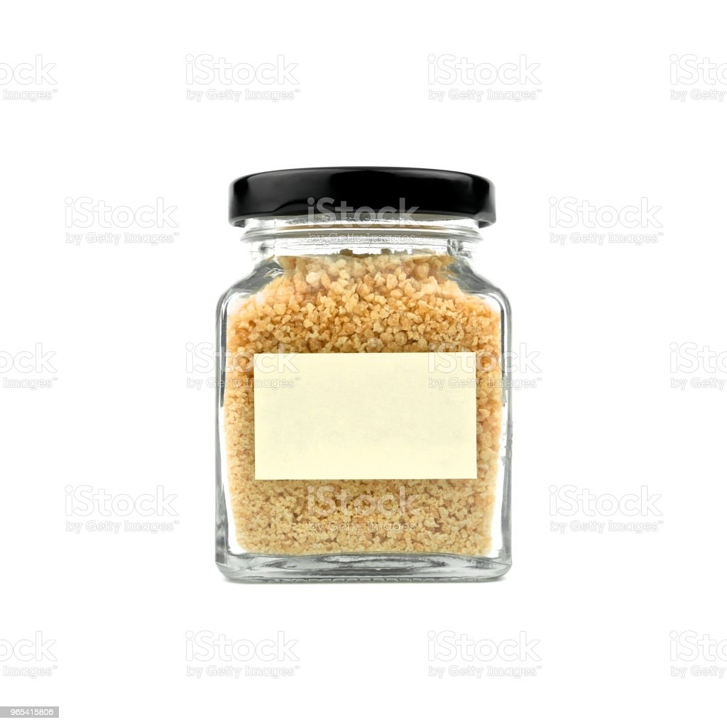 Brown sugar in a glass bottle isolated on white background. Granulated sugar. Empty yellow stick note paper and black lid. Modern and stylish. Close up. zbiór zdjęć royalty-free
