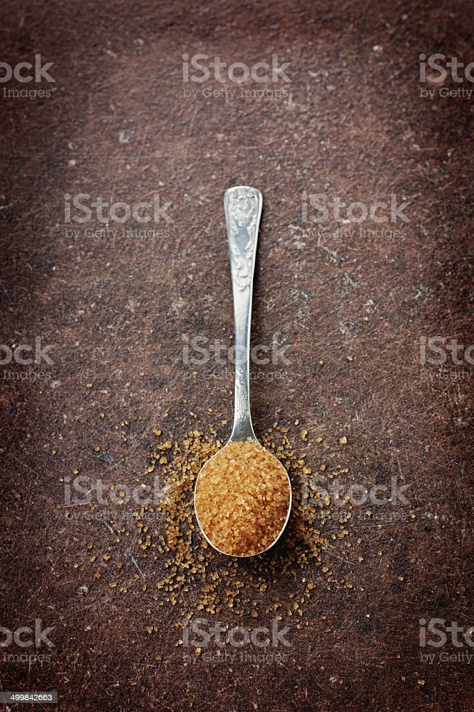 brown sugar in a spoon on a vintage surface stock photo