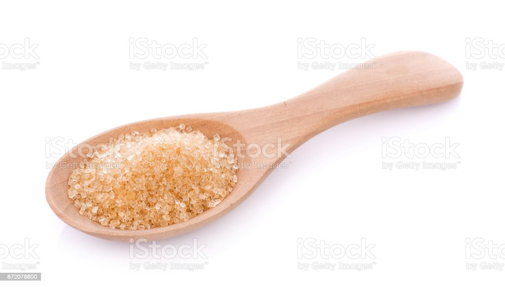 Brown sugar in wooden spoon on white background stock photo