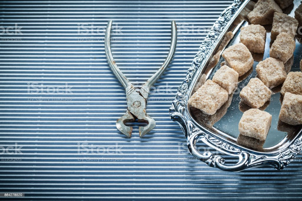 Brown sugar pliers tray on striped background royalty-free stock photo