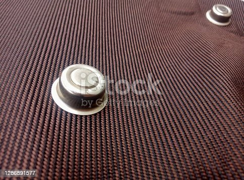 silver round metal studs.  the base of a brown clothing suitcase