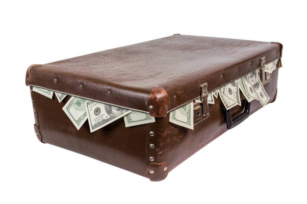 A brown suitcase with sticking out dollar banknotesold. Closed, laying on side and isolated on white background. stock photo