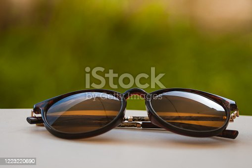 Brown sunglasses leaning against a white table with grass background in warm tones.