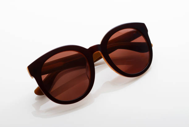 Brown sunglasses isolated on light glossy background close-up stock photo