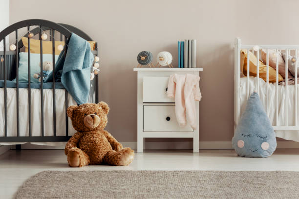 Brown teddy bear on the wooden floor of scandinavian baby bedroom interior with white nightstand and cribs