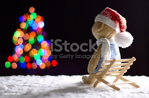 istock Brown teddy bear wearing scarf and santa hat sitting on wooden bench with snow in winter looking at colorful bokeh lights of Christmas tree. 1069058150