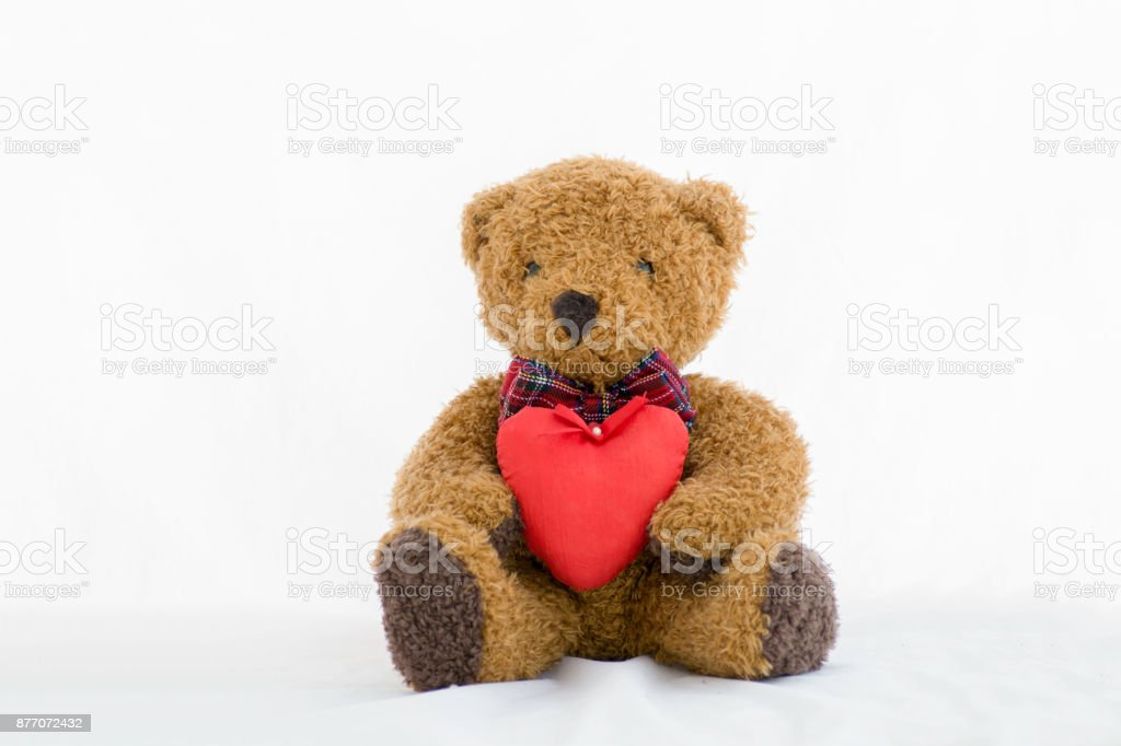 Brown teddy bear with red heart on a white background stock photo