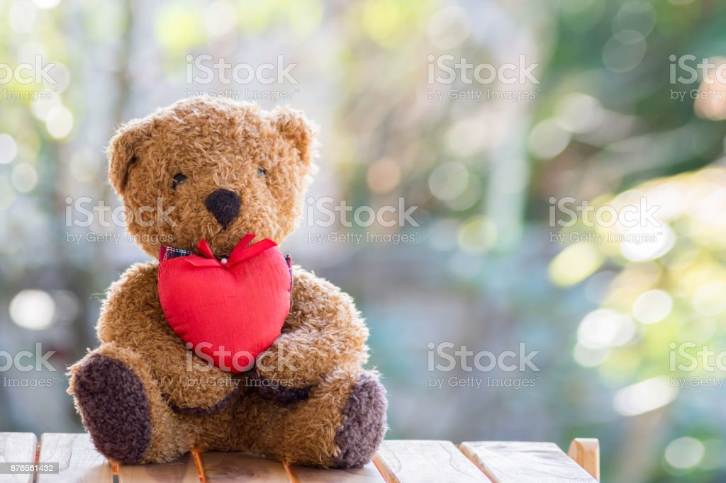 Brown teddy bear with red heart on the wooden floor. stock photo