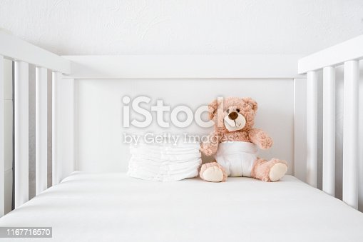 Brown teddy bear with white diaper sitting in baby bed.