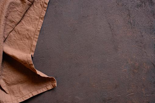 Brown textured kitchen background with linen napkin, copy space