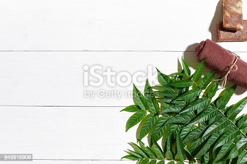 istock Brown towel and natural coffee soap on white wooden table, top view 849916906