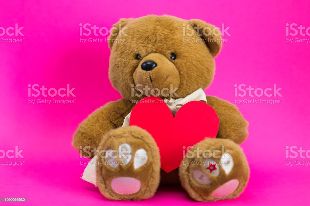 Brown toy cartoon teddy bear sits on a pink background with red paper...