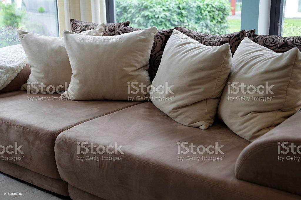 Braun, gepolsterten sofa mit beige Kopfkissen – Foto