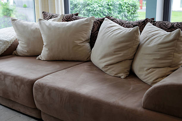 Brown upholstered sofa with beige pillows stock photo