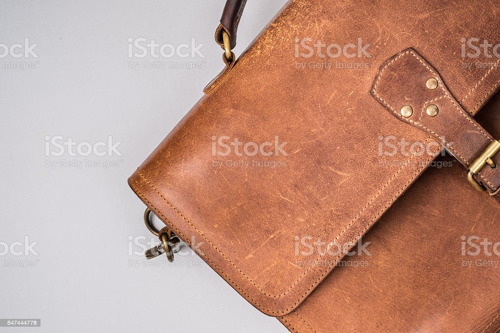 Brown Vintage leather briefcase with strap and brass buckle, stock photo