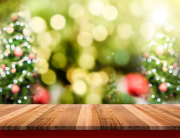 brown wood table top with abstract blur christmas tree - christmas green stock photos and pictures