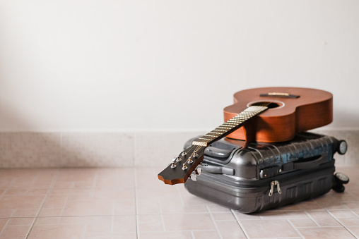 istock Brown wooden acoustic guitar put on the gray color luggage in the room for traveling all around the world and sing song with acoustic guitar music 871193202