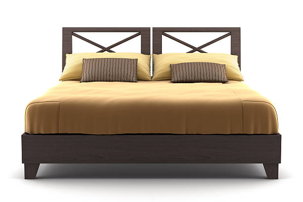 Brown wooden bed with tan sheets on a wooden surface stock photo