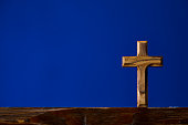 Brown wooden crucifix on blue background