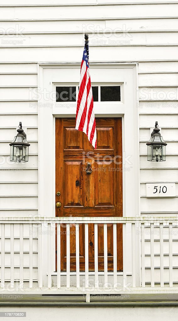 brown wooden door in white wall with US flag royalty-free stock photo