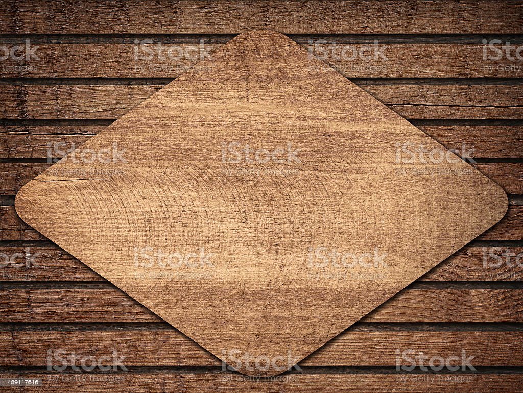 Brown wooden lozenge with shadow on planks wall stock photo