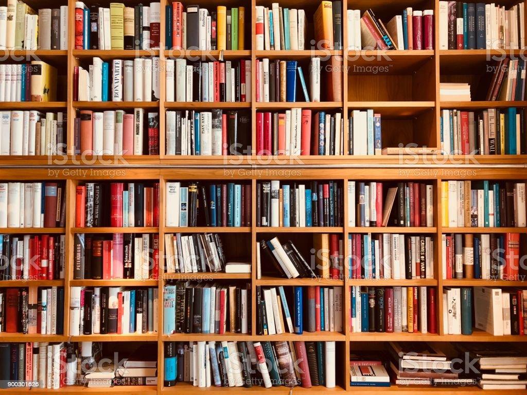 Anaqueles de madera marrón completamente lleno con los libros en una biblioteca foto de stock libre de derechos