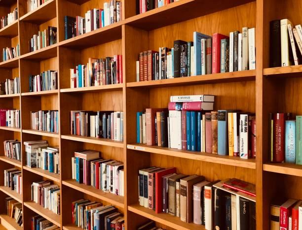braune hölzerne regale voll gepackt mit büchern in einer bibliothek - deutsche bibliothek stock-fotos und bilder
