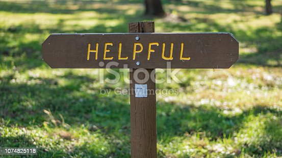 Brown wooden sign in grassy field with helpful written on it